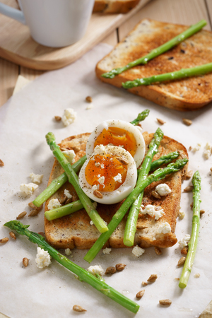 booting: steamed asparagus, soft boiled egg and crumbled feta cheese on toast bread
