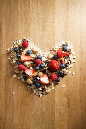 healthy snack: granola healthy snack with fresh berry in heart shaped Stock Photo