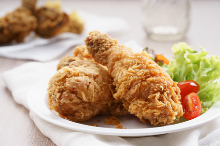 fried chicken with fresh vegetable in white plate on wooden table Foto de archivo
