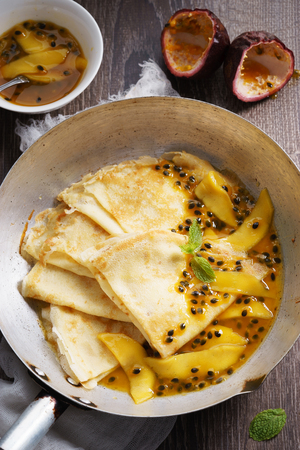 pan tropical: crepes with passion and mango syrup in flying pan