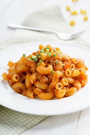 pasta sauce: macaroni pasta in tomato sauce with chop meat decorated with scallion on a wooden table