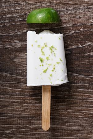 ice cream bar: coconut ice pops ,coconut ice cream bar, with fresh green lime zest on wooden background