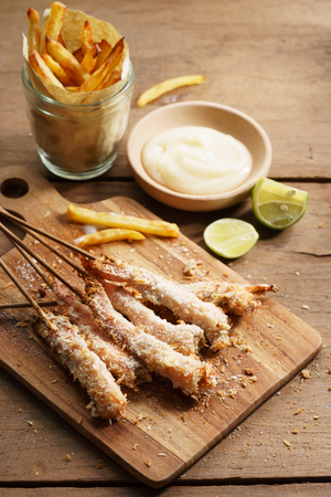 crumbed prawn skewers with potato fries on wooden table Stock Photo