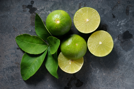 fresh limes with slice and leaves on dark background Foto de archivo