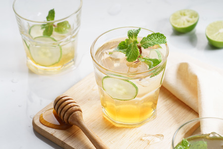 lime and honey iced drinks with cucumber sliced on white marble table