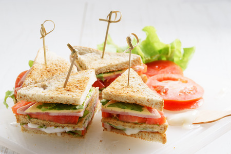 whole wheat toast: Sandwich of whole wheat bread with ham, cheese and fresh tomato, triangle cut, three layers sandwich bread Stock Photo