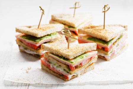 whole wheat bread: Sandwich of whole wheat bread with ham, cheese and fresh tomato, triangle cut, three layers sandwich bread Stock Photo