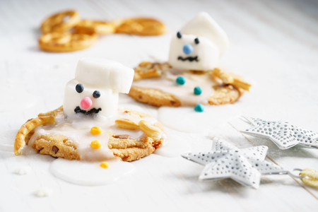 Melting snowman biscuits, marshmallow snowman decorates on cookies for holiday dessert Stock Photo