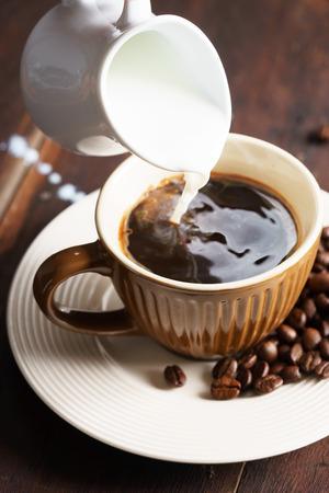 Tasse heißen Kaffee mit Milch auf Holztisch mit Kaffeebohnen Standard-Bild