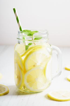 lemonade in jar with fresh lemon sliced and sprig of mint