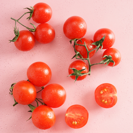 lycopene: fresh tomato on pink background with drops of dew