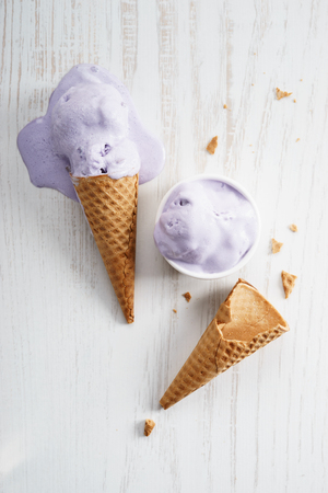 melting purple color ice cream on waffle cone Stock Photo