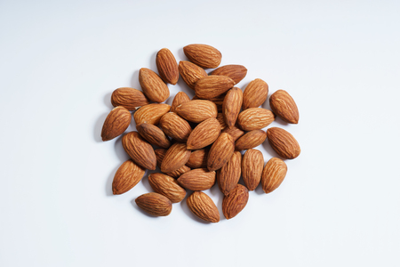 group of almonds arranged in circle shape on white background, top view close up
