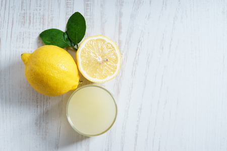 lemon juice with fresh sliced pieces on white wooden background Stock Photo