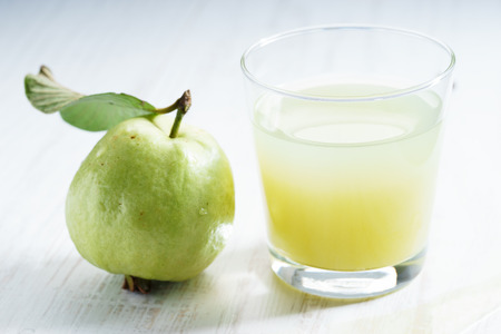 guava juice with fresh sliced pieces on white wooden background