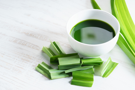fresh pandan leaves and pandan juice on white wooden background
