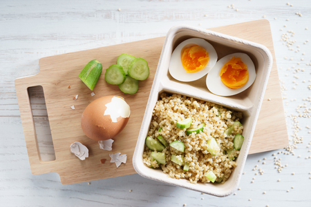 quinoa salad with boiled egg in paper food container, top view Stock Photo
