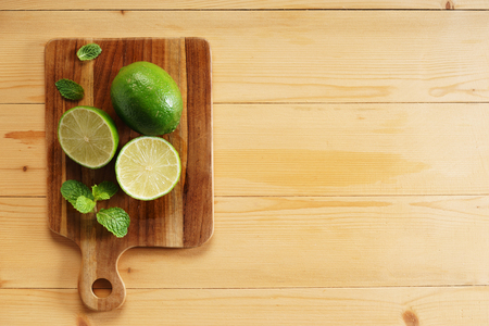 fresh green lime and slices on wooden plank Stock Photo