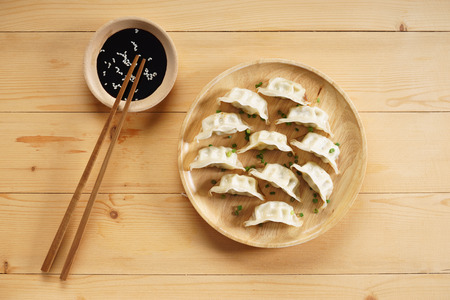 Japanese gyoza, fried dumplings, with soy sauce on wooden plate Stock Photo