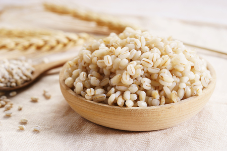 Cooked peeled barley grains in wooden plate