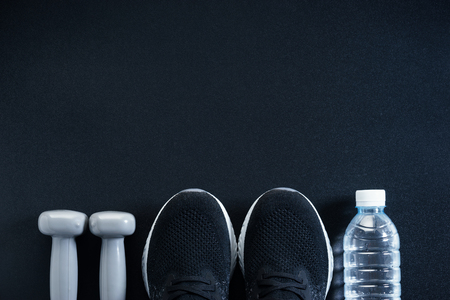workout concept with black sneaker, gray dumbbells and bottle of water