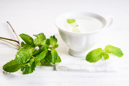 Hot herbal mint tea in white cup with leaves Banco de Imagens