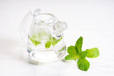 Hot herbal mint tea in white cup with leaves