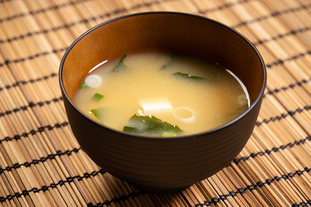 Miso soup with tofu and seaweed in brown Japanese bowl