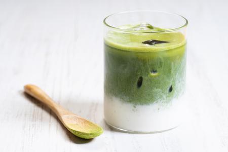 Iced Green Tea Latte mit Doppelschicht auf weißem Holzuntergrund