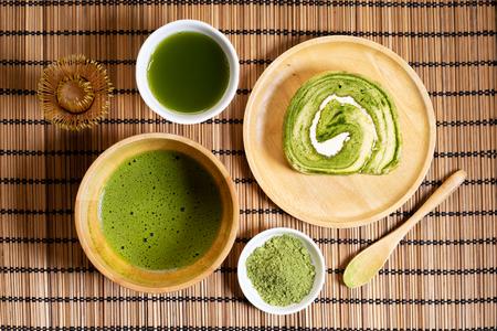 matcha green tea powder with matcha drinks and matcha swiss roll dessert on wooden mat, top view 免版税图像