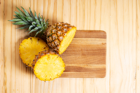 fresh cut pineapple on wooden plank