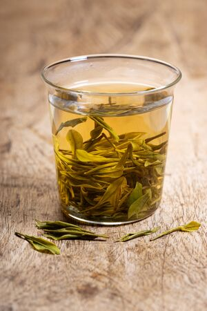 glass of tea with tea leaves on wooden background