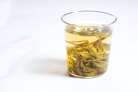 glass of tea with tea leaves on white background