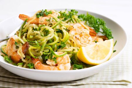 zucchini pasta with shrimps on white plate