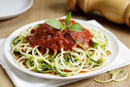 zucchini pasta with tomato sauce in white plate on wooden table