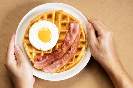 Waffles with fried egg and bacon on white dish