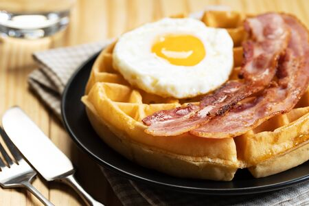 Waffles with fried egg and bacon on black dish, closeup