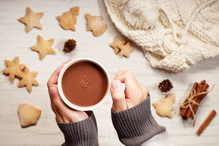 Man's hands holding hot chocolate in white cup with star shaped cookies on Christmas table background. Top view.
