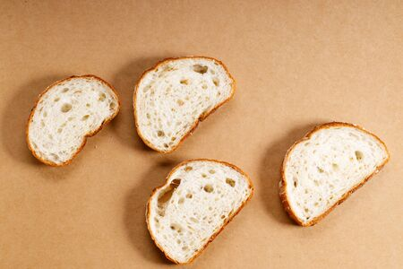 sliced whole grain bread in a row on brown background, top view Stock fotó