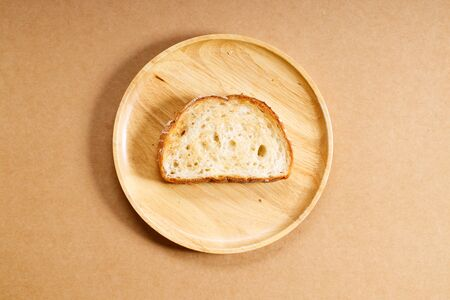 toasted plain whole grain bread on wooden dish, top view