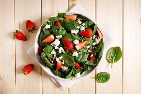 Healthy spinach salad with strawberries, feta cheese and almond on a white bowl on wooden table background. Diet menu. top view. Stock fotó