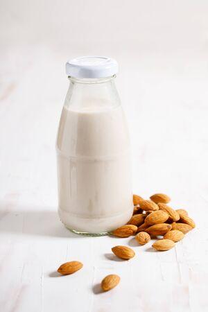 Almond milk in glass bottle with fresh almond nuts on white wooden background Standard-Bild