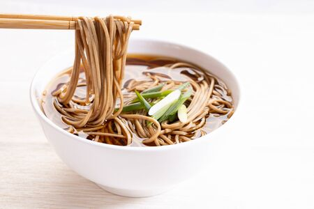 soba noodles, zaru soba, in white bowl with bamboo chopsticks