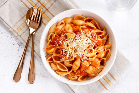 Pasta conchiglie with tomato sauce and parmesan cheese in white dish, simple meal concept