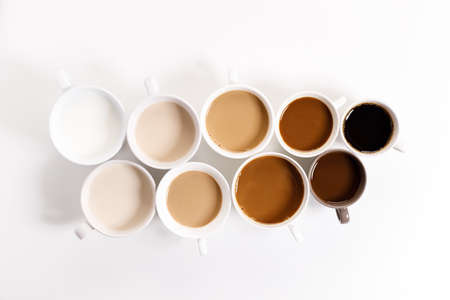 cups of coffee on white background with color gradient of coffee by varing amount of milk,top view