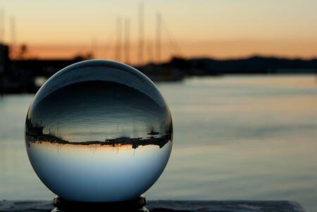 Crystal ball met boten en reflectie zonsondergang Stockfoto