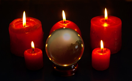 to foresee: Crystal ball and five red candles burning Stock Photo