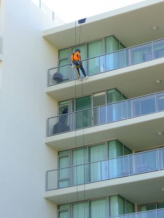 abseil: Worker abseiling on highrise apartments