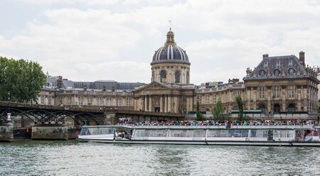 sightseers: Tourist boat cruise on River Seine, Paris, going past historic buildings