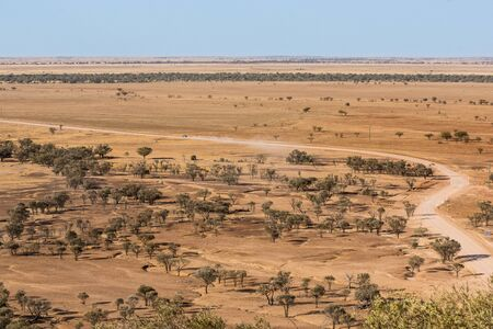 driving conditions: Car driving on dry, dusty road in drought conditions in western Queensland, high view point
